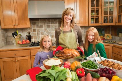 Mother and children preparing Thanksgiving dinner in home kitchen