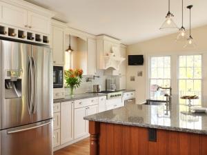 Stainless steel refrigerator in white kitchen