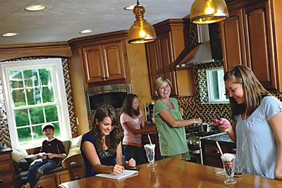 family of mother and children in kitchen cooking laughing and smiling and doing paperwork or school work at counter image