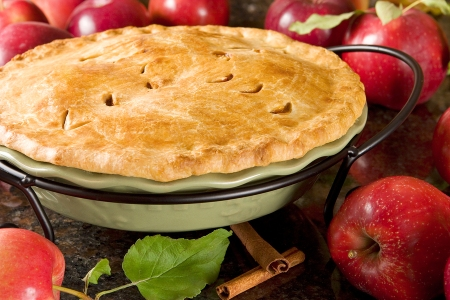 apple pie with red apples on countertop