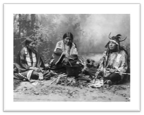 Sioux indians (mid-1800s) gathered around the cooking fire