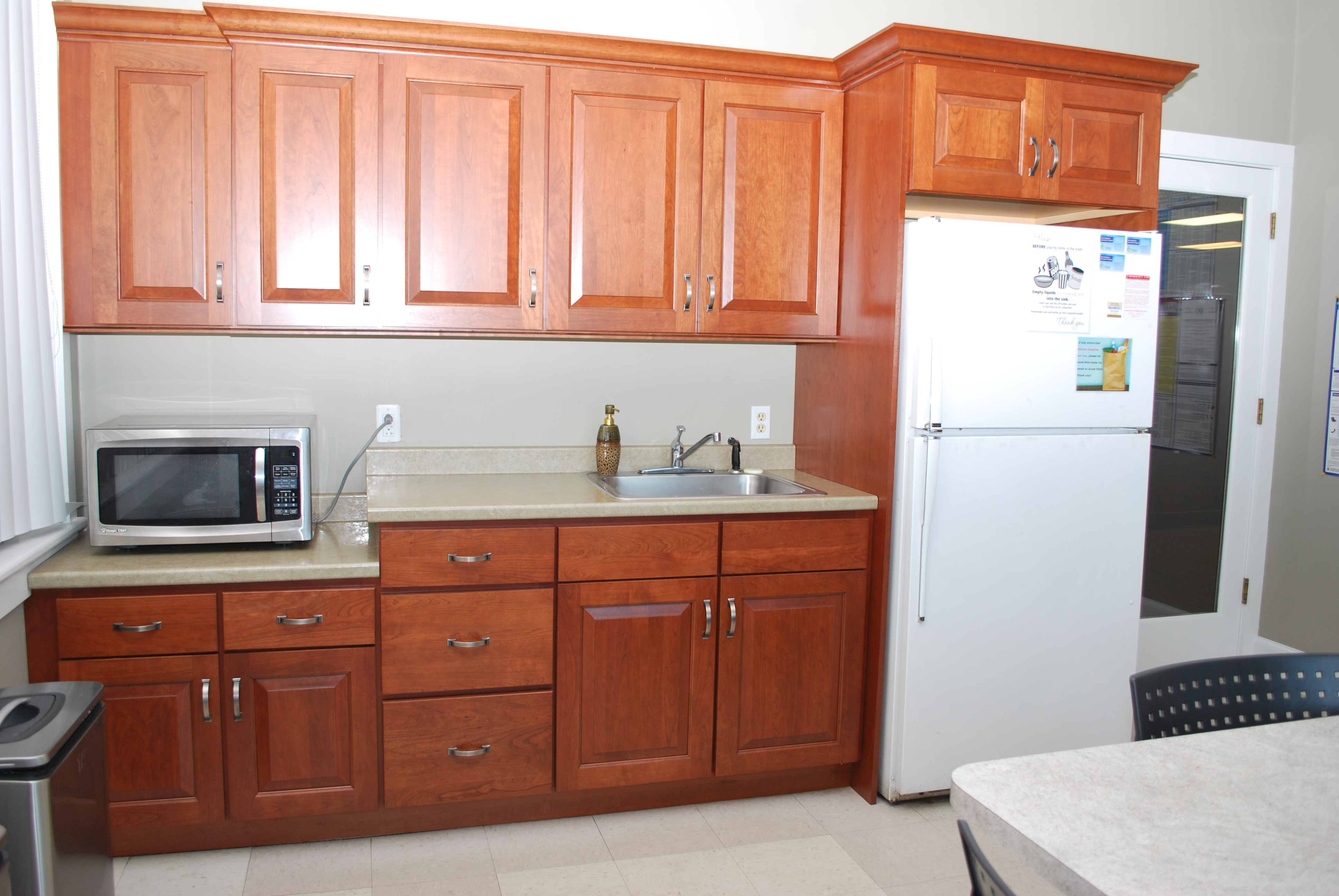 AFTER - office break room with cherry wood cabinetry doors and laminated cherry veneer covering other surfaces.