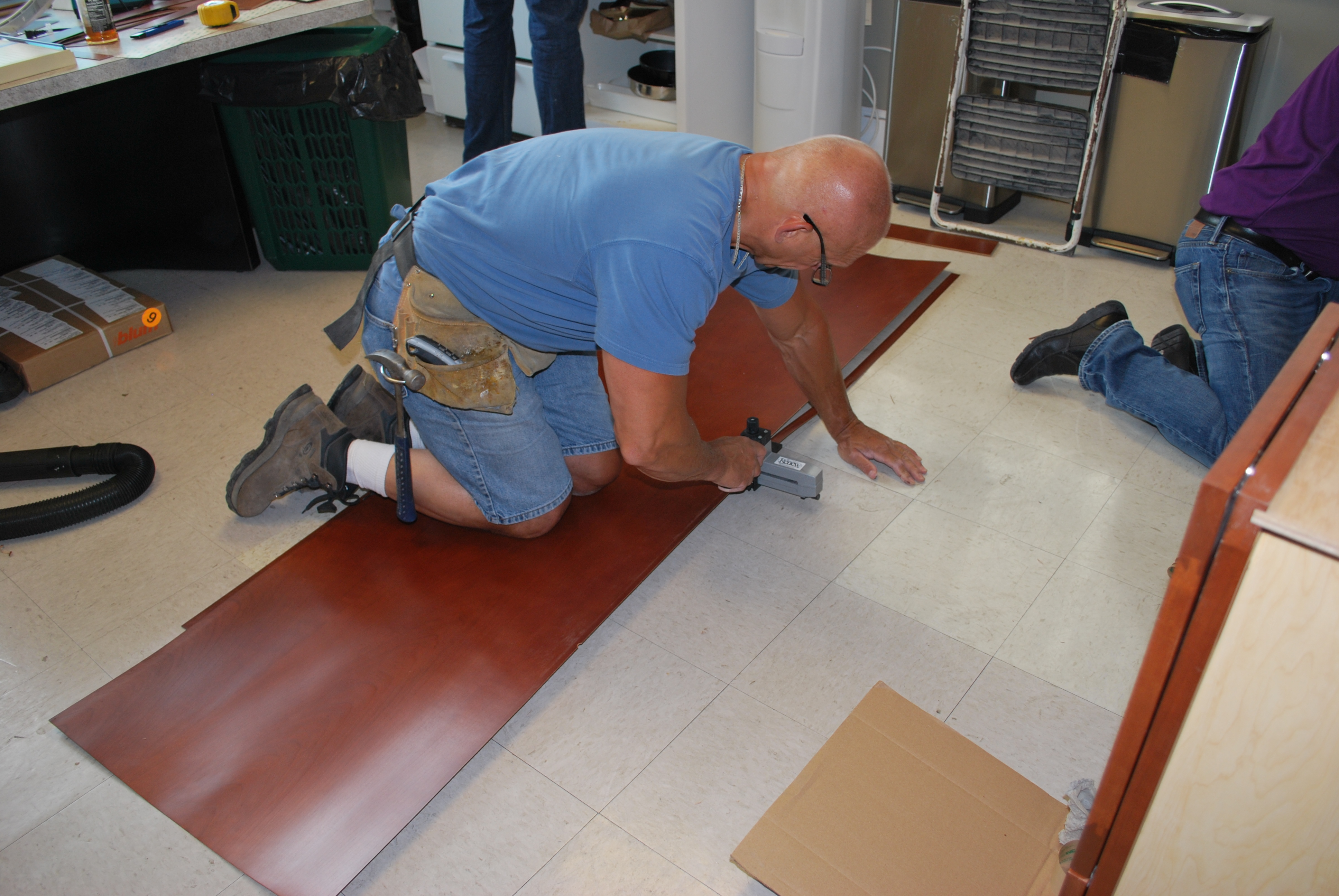 DURING REFACING - workman prepares sections of cherry laminate.