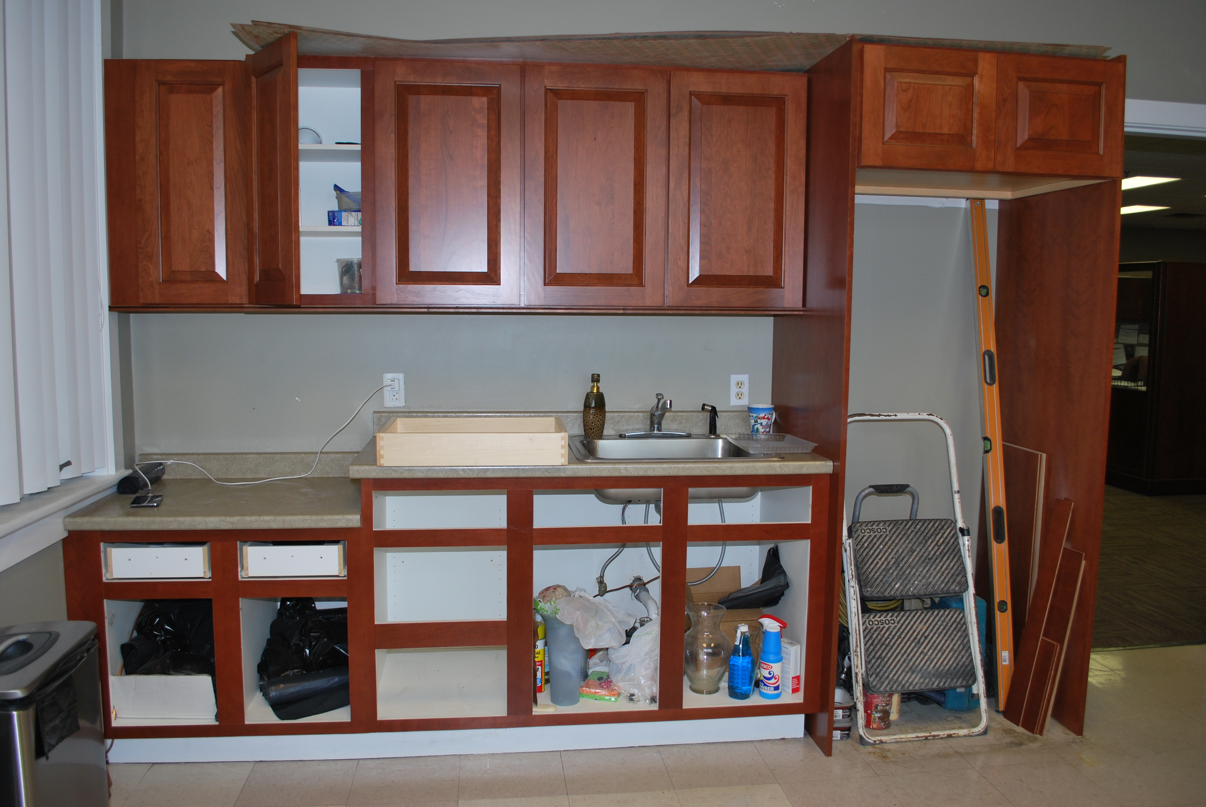 DURING REFACING - contents can be left in the cabinets. But the drawers were removed and we selected to replace the originals with new wood drawer boxes in addition to the new cherry wood drawer fronts.