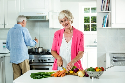 Portrait of happy senior woman cutting vegetables in kitchen
