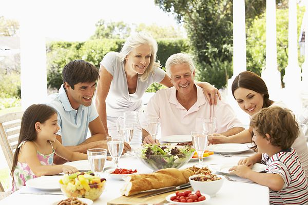 Family eating meal outside in garden