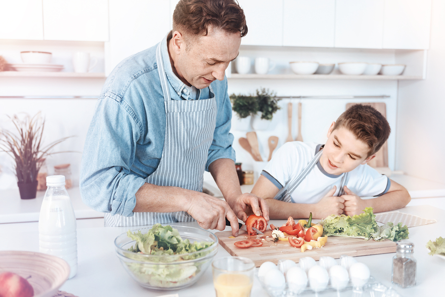 Man teaching boy food prep at kitchen island